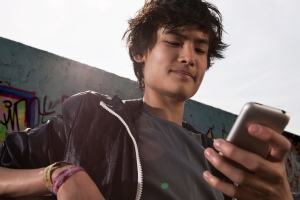 Germany, Berlin, Teenage boy using mobile phone