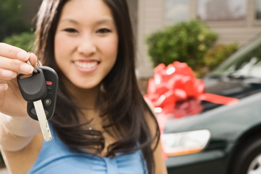 Asian teenager holding keys to new car