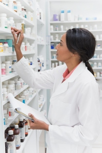 African pharmacist looking at bottle on shelf