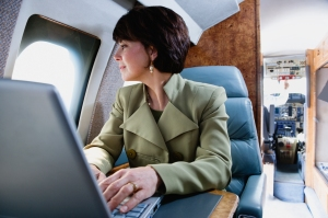 Businesswoman with laptop on private airplane