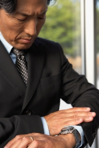 Asian businessman looking at wrist watch