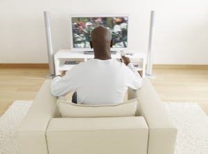 Man watching television holding the remote