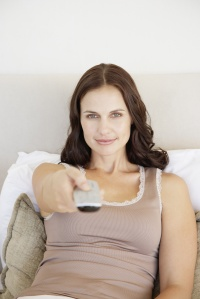 Woman sitting in bed with the television remote