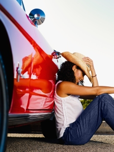 Mixed race woman leaning on red convertible