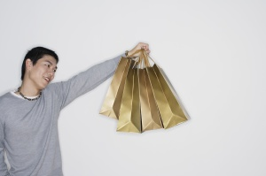 Man indoors holding shopping bags