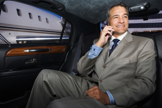 Businessman talking on his cell phone in limo