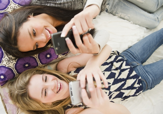 Teenage girls text messaging on cell phones
