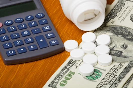 Open bottle of pills on top of money focus on bottom pills and calculator