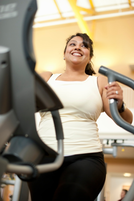Woman using elliptical machine in gym