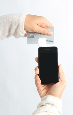 Woman uses a square card reader to make a transaction through her smart phone
