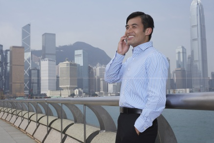 Young business man on bridge talking on mobile phone smiling