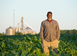 Three-quarter length selective focus view of a mature African-American male farmer standing in a corn field and smiling at the camera