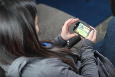 Teenager uses iPhone to use educational app.