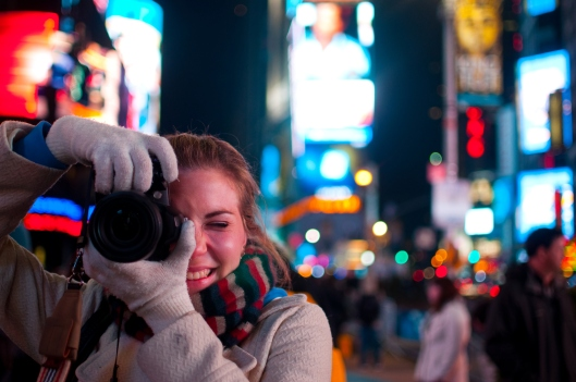 Head and shoulders view of a 20-25 year-old Caucasian woman holding up a camera taking a photo in Times Square,  Manhattan