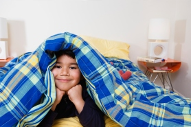 Boy under blanket looking at camera