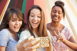 Teenage girls taking self-portrait with cell phone