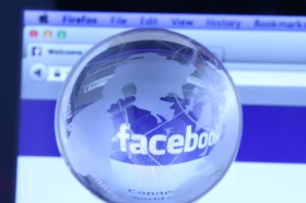 Facebook webpage with glass globe. As of today, Facebook is the largest social media network on the web