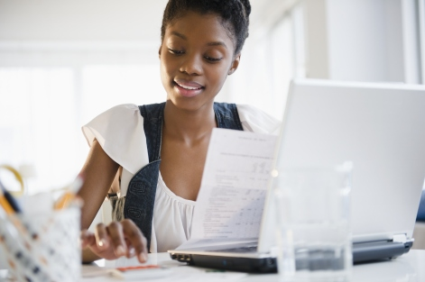 Cropped head-and-shoulders view of a young African-American woman paying bills online